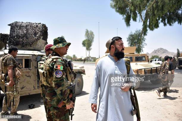 Afghan security personnel stand guard along the road amid ongoing fight between Afghan security forces and Taliban fighters in Kandahar on July 9,...