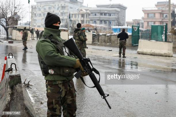 Afghan security personnel stand guard an area following a suicide attack near the Marshal Fahim Military Academy base in Kabul on February 11, 2020....