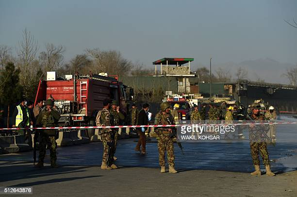 Afghan security personnel stand guard as firefighters clean the site of a suicide bombing near the gate of Ministry of Defence in Kabul on February...