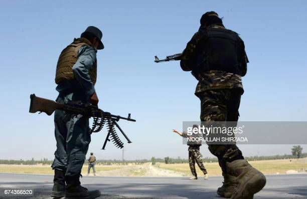 Afghan security personnel stand guard at a checkpoint on the outskirts of Jalalabad on April 28 2017 Two US troops were killed and one was wounded...
