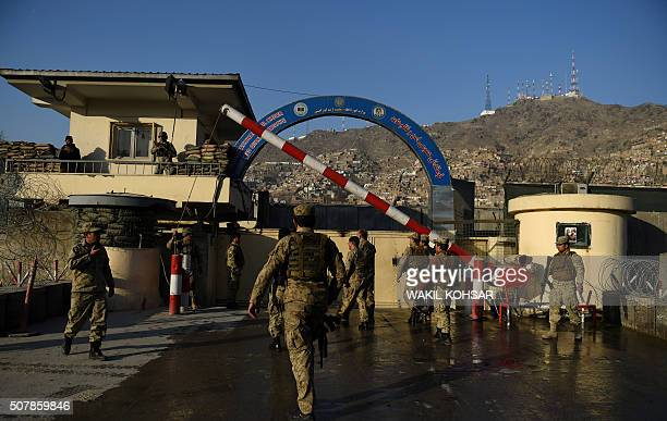 Afghan security personnel stand guard near the site of a suicide attack at the entrance to a police base in Kabul on February 1 2016 A Taliban...