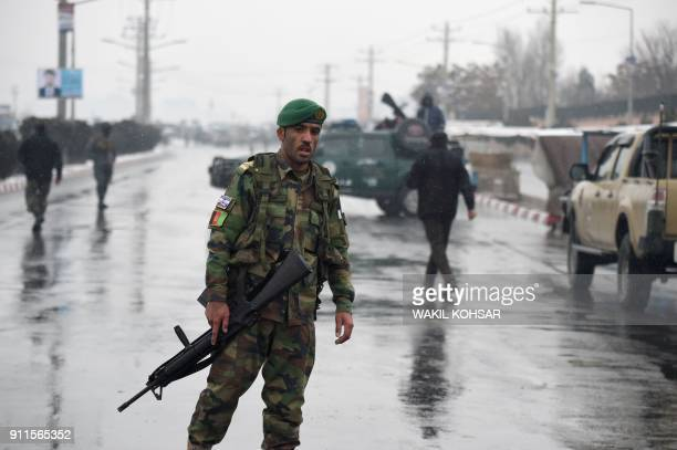 TOPSHOT Afghan security personnel stand guard near the site of an attack near the Marshal Fahim Military Academy base in Kabul on January 29 2018...