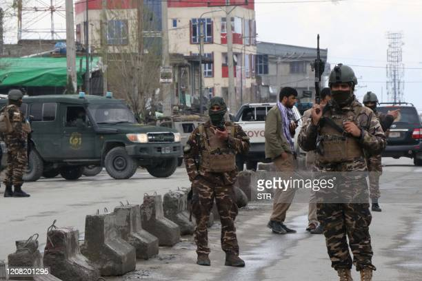 Afghan security personnel stand guard near the site of an attack to a Sikh temple in Kabul on March 25 2020 The Islamic State group has claimed an...