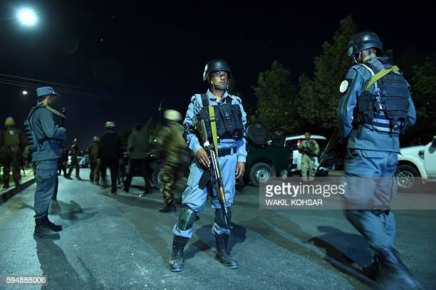 TOPSHOT Afghan security personnel stand guard near the site of explosion that targeted the elite American University of Afghanistan in Kabul on...