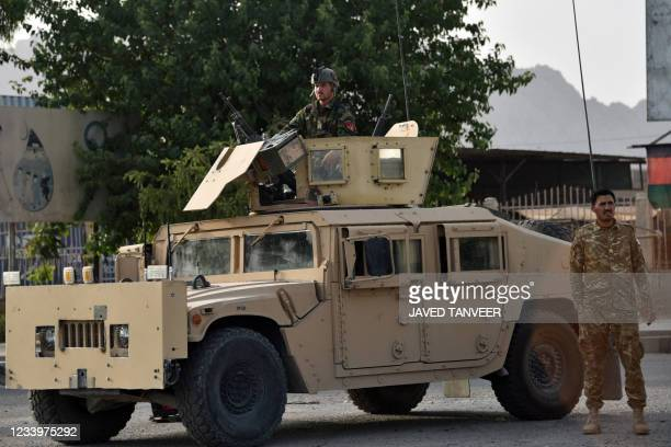 Afghan security personnel stand guard on a Humvee vehicle along a road in Kandahar on July 14, 2021.