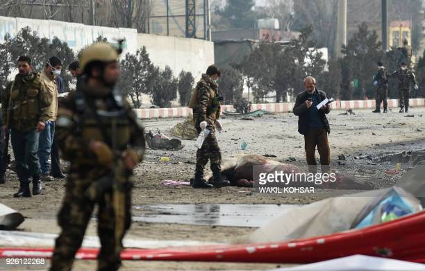 Afghan security personnel stand near a dead horse slaughtered by an Afghan butcher after suffering injures at the site of suicide car bomb attack...
