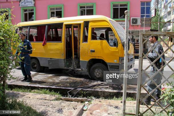 Afghan security personnel stand near the a damage bus carrying university students at the site of the successive bomb blasts in Kabul on June 2 2019...