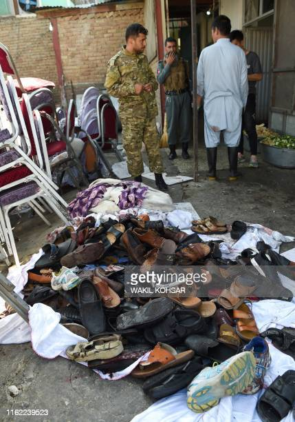 Afghan security personnel stand next to a pile of shoes and sandals of victims outside a wedding hall after a deadly bomb blast in Kabul on August...