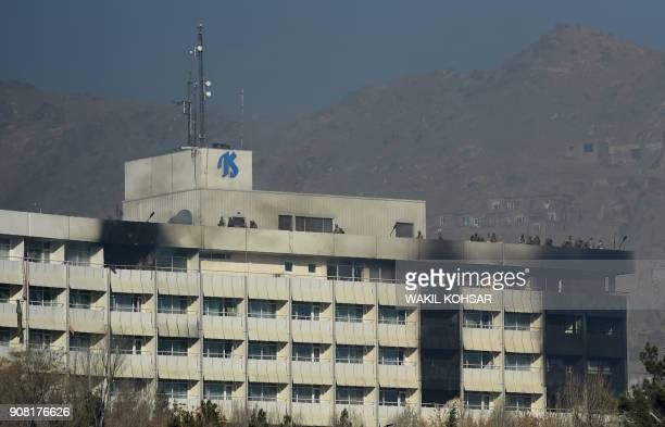TOPSHOT Afghan security personnel take position at the rooftop of the Intercontinental Hotel during a fight between gunmen and Afghan security forces...
