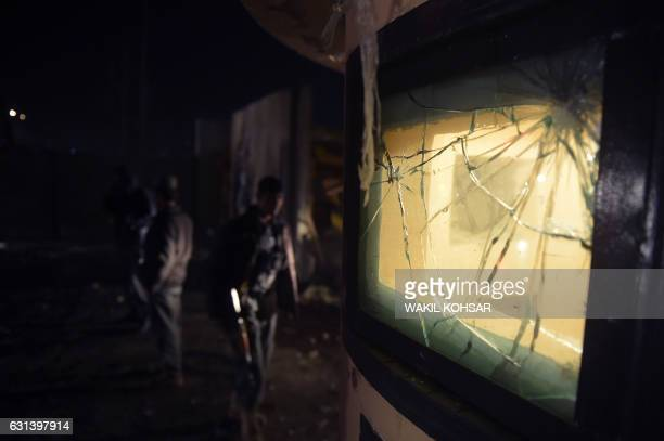 TOPSHOT Afghan security personnel walk past a damaged gate after twin blasts struck near the Afghan parliament in Kabul on January 10 2017 Twin...