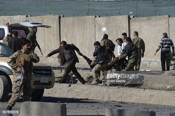 TOPSHOT Afghan security personnels carry a victim at the site of a suicide car bomb next to a police base in Kabul on February 1 2016 A suicide car...