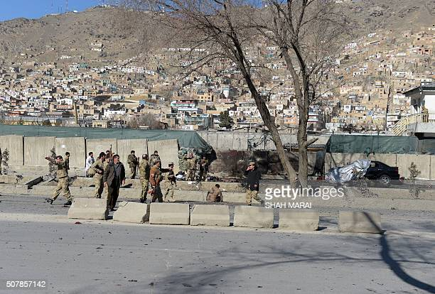 Afghan security personnels gather as victims are treated at the site of a suicide car bomb next to a police base in Kabul on February 1 2016 A...