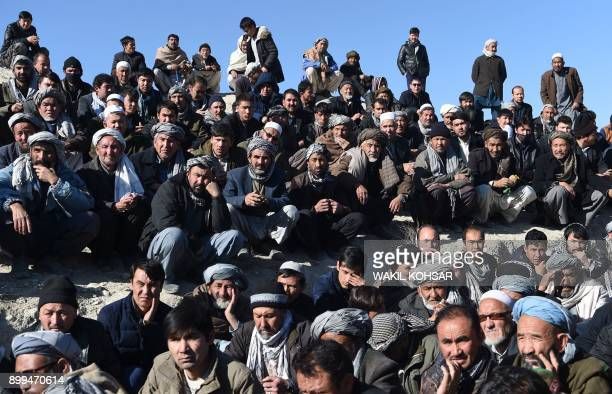 Afghan Shiite mourners and relatives attend a burial ceremony for the one of the 41 victims of a bomb attack on a Shiite cultural center in Kabul on...