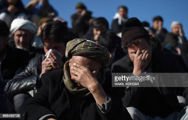 Afghan Shiite mourners and relatives weep during the burial ceremony for the one of the 41 victims of a bomb attack on a Shiite cultural center in...