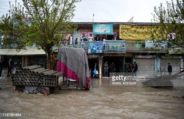 Afghan shopkeepers look on from the doorstep of their shops as heavy rain falls in Kabul on April 152019