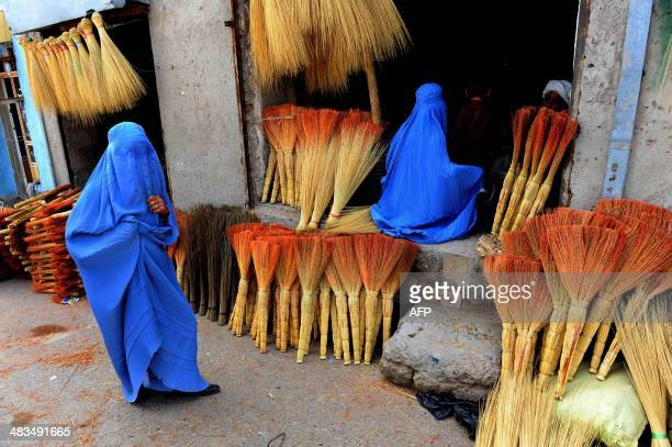 Afghan shoppers look for brooms at a roadside shop in Herat on April 9 2014 Leading candidates in Afghanistan's presidential election voiced concern...