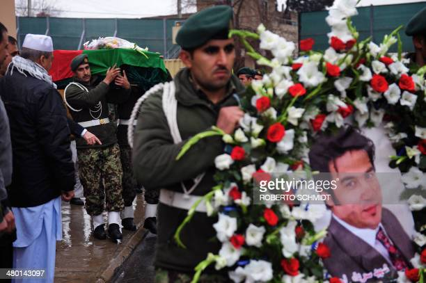 Afghan soldiers carry the casket of slain AFP reporter Sardar Ahmad as they leave a local hospital during funeral ceremonies in Kabul on March 23...