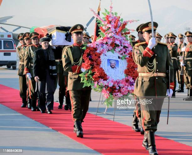 Afghan soldiers carry the coffin of slain Japanese physician Tetsu Nakamura at a ceremony at an airport in Kabul on Dec. 7 before transporting his...