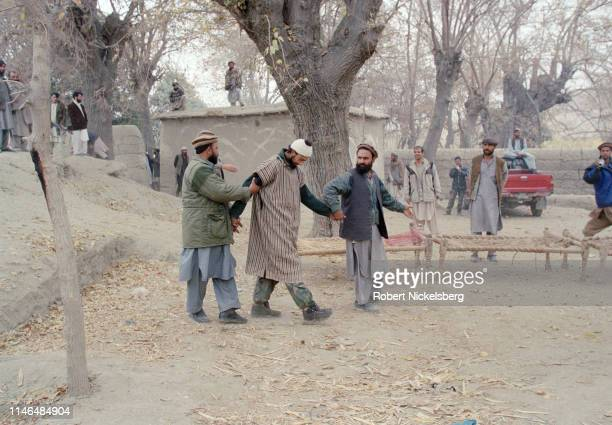 Afghan soldiers present an Arab fighter belonging to al Qaeda who had surrendered in the battle around the Tora Bora region in Agom, Afghanistan on...