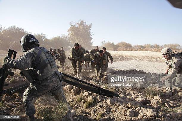 Afghan soldiers race wounded civilians towards a US Army medical evacuation helicopter in Kandahar The Dustoff crews from Charlie Company 6th...