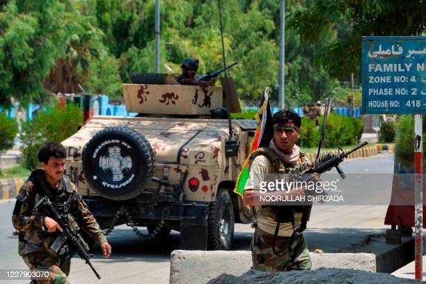 Afghan soldiers take up position outside a prison during an ongoing raid in Jalalabad on August 3, 2020. - At least 29 people were killed in a raid...