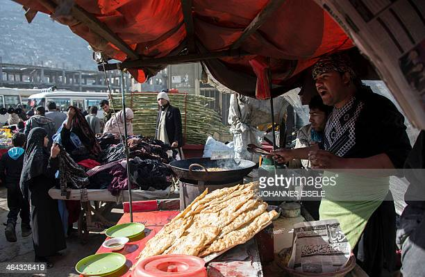 Afghan street vendor Zabiullah sells Bolani from his stall in Kabul on January 22 2014 Bolani is a flatbread from Afghanistan and has a thin crust...