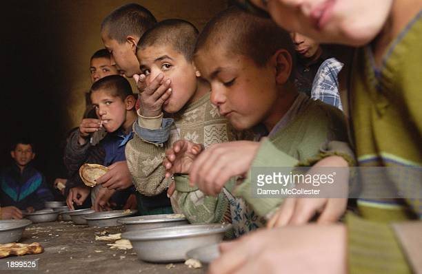 Afghan students eat a lunchtime meal of rice and bread April 5 2003 at the Aschiana School in Kabul Afghanistan The Aschiana School is a school...