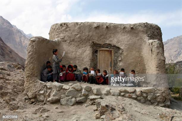 Afghan students recite Islamic prayers in a makeshift outdoor classroom in a small village September 2 2007 in the remote Wakhan Corridor Afghansitan