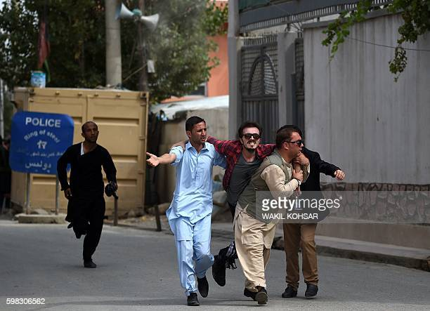 Afghan supporters carry a wounded colleague during clashes with loyalists of vicepresident general Abdul Rashid Dostum during the King Habibullah...