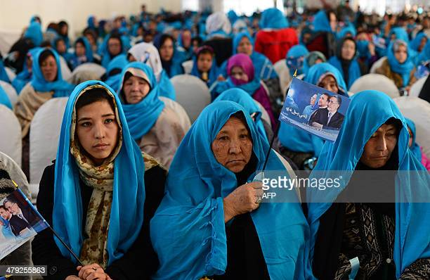 Afghan supporters hold flags bearing the image of Afghan second vicepresidential candidate Habiba Surabi as she appears during an election rally in...