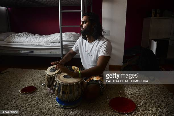 Afghan surfer Afridun Amu plays a typical Afghan percussion instrument called tabla in his room at the first Afghan surf championship organized by...