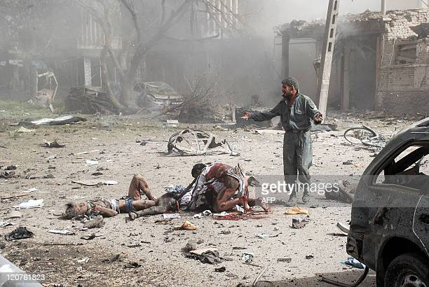 Afghan survivors stand at the scene of a suicide bombing outside the Indian Embassy in Kabul on July 7 2008 A suicide bomber rammed an...