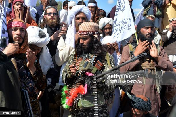 Afghan Taliban militants and villagers attend a gathering as they celebrate the peace deal and their victory in the Afghan conflict on US in...