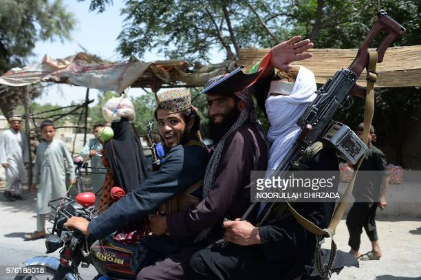 Afghan Taliban militants ride a motorbike as they took to the street to celebrate ceasefire on the second day of Eid in the outskirts of Jalalabad on...