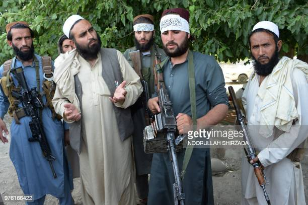 Afghan Taliban militants stand with residents as they took to the street to celebrate ceasefire on the second day of Eid in the outskirts of...