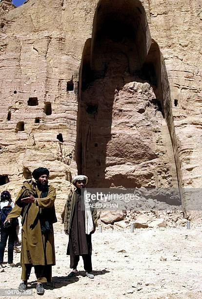 Afghan Taliban militia's officials stand in front of the completely destroyed tallest standing Buddha statue in Bamiyan city in central Afghanistan...