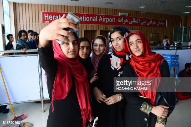Afghan teenagers from the Afghanistan Robotic House take pictures with a mobile phone at Herat International Airport on July 13 before embarking for...