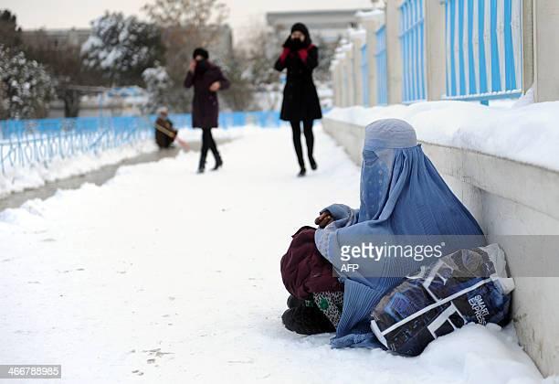 Afghan university students walk past a burqaclad woman sitting on a snowy sidewalk in Mazarisharif on February 3 2014 During the winter months many...
