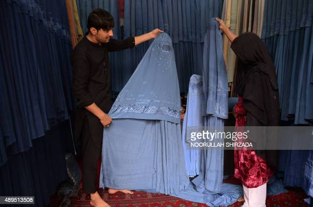 Afghan vendor shows a traditional 'burqa' to a customer at a shop ahead of the sacrificial Eid alAdha festival in Jalalabad on September 22 2015...