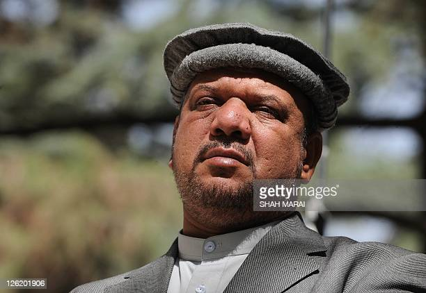 Afghan vice President Mohammad Qasim Fahim listens to unseen Afghan President Hamid Karzai during a press conference at the Presidential Palace in...