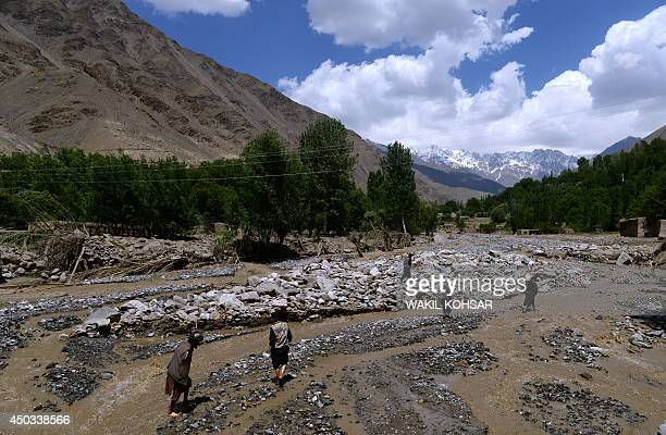 Afghan villagera cross a river as they walk through the site of a landslide following flooding in the GuzargaheNur district of Baghlan province of...