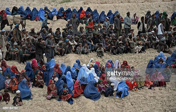 Afghan villagers affected by landslides wait to get aid supplies during a distribution in the Argo district of Badakhshan on May 4, 2014. Aid groups...