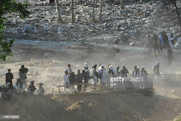 Afghan villagers and rescuers look on during a search for earthquake victims in a village at Burka district the worsthit area in the province of...