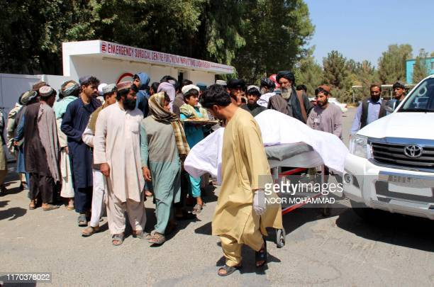 Afghan villagers carry a dead body on a stretcher outside a hospital following an airstrike in Lashkar Gah the capital of Helmand province on...