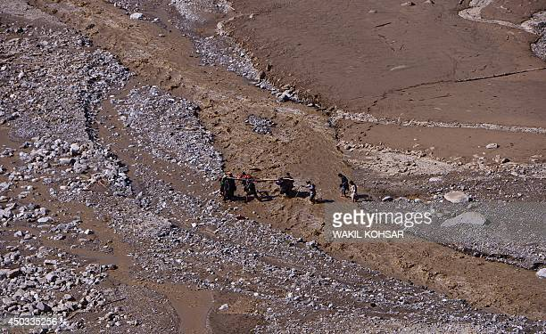 Afghan villagers cross a river as they carry the body of a resident killed in a landslide following flooding in the GuzargaheNur district of Baghlan...