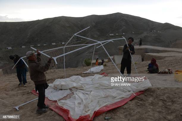 Afghan villagers erect a relief tent in Argo district of Badakhshan province on May 3, 2014 after a massive landslide May 2 buried a village. Rescue...