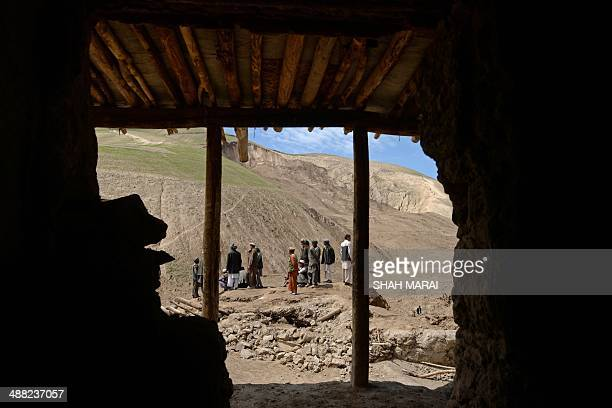 Afghan villagers look on at the scene in the landslide-hit Aab Bareek village in Argo district of Badakhshan on May 5, 2014. Rescue teams abandoned...