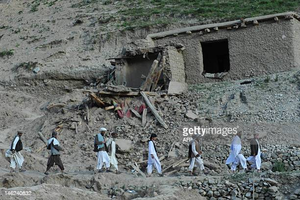 Afghan villagers search for earthquake victims past a collapsed house in a village at Burka district the worsthit area in the province of Baghlan...