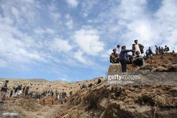 Afghan villagers search through dirt and debris at the scene in the landslide-hit Aab Bareek village in Argo district of Badakhshan on May 5, 2014....