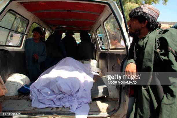 Afghan villagers sit on the back of a vehicle carrying dead bodies to a hospital following an airstrike in Lashkar Gah the capital of Helmand...